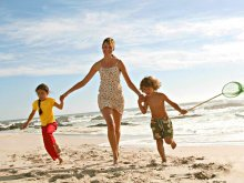 image woman-and-children-running-on-the-beach-jpg